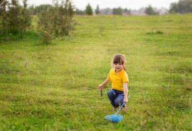 beautiful smiling girl child 4-5 years old in a yellow T-shirt and jeans with a blue net is catching butterflies in a green meadow.