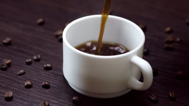 hot black coffee and cream is poured into a cup on wooden background
