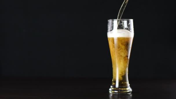 Pivo je nalití do sklenice na černém pozadí
