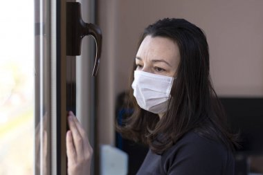 Sad woman with mask on quarantine looking out the window. Isolation in the house in Quarantine concept during a virus pandemic