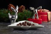 Čokolády na pozadí figurek vánočních sobů, dárky a věnec s kužely.