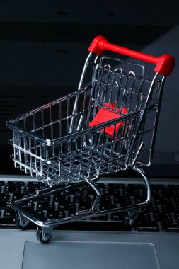 a tiny shopping cart on isolated background