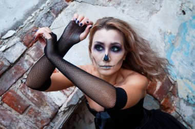 beautiful young woman in costume on Halloween, day. broken brick staircase