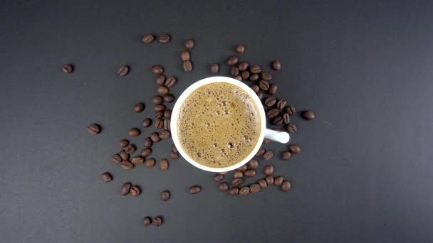 Top view of hand take cup of coffee on coffee beans black background