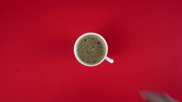 Top kilátás a kezét, hogy egy csésze kávét a kávébab piros háttér