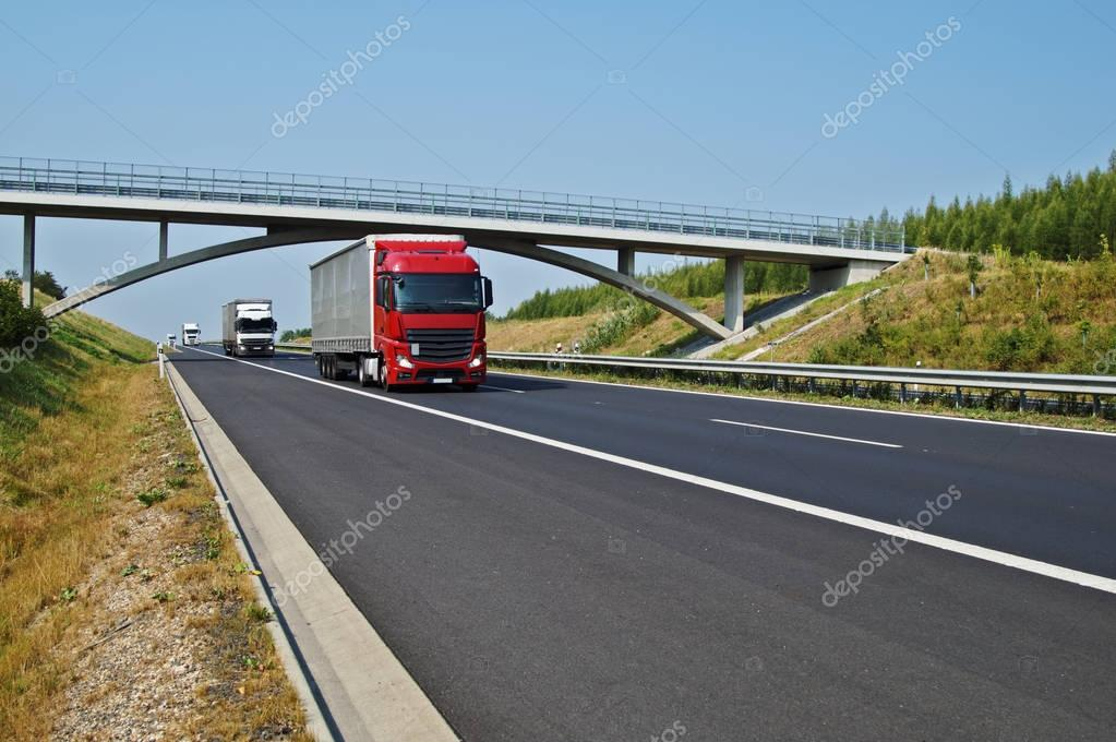 Trucks on asphalt highway goes under a concrete bridge in the countryside. Sunny day with blue sky.