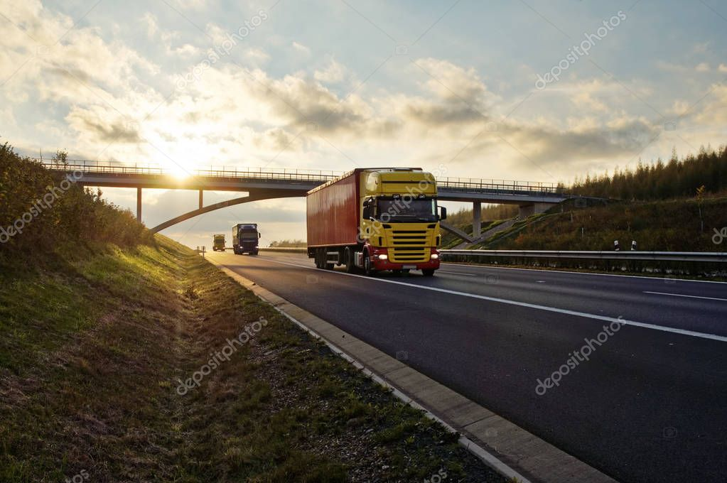 Trucks passing under a concrete bridge on the asphalt road at sunset.