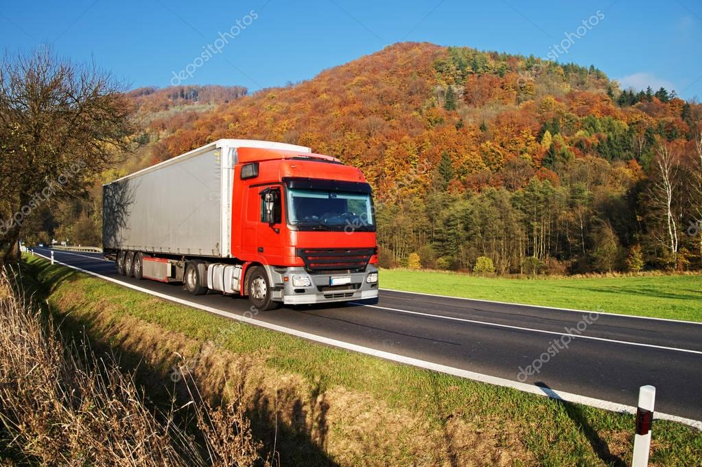 Red truck on asphalt road under forested mountain of glowing autumn colors. Clear sunny day with blue skies.