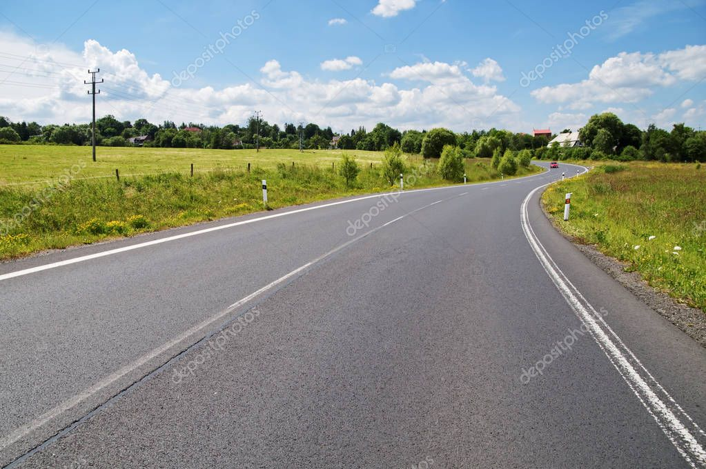 Empty asphalt road with a double bend between flower meadows in the countryside. Red car on the road in the distance. Village among the green leafy trees background. Clear sunny day with blue skies an