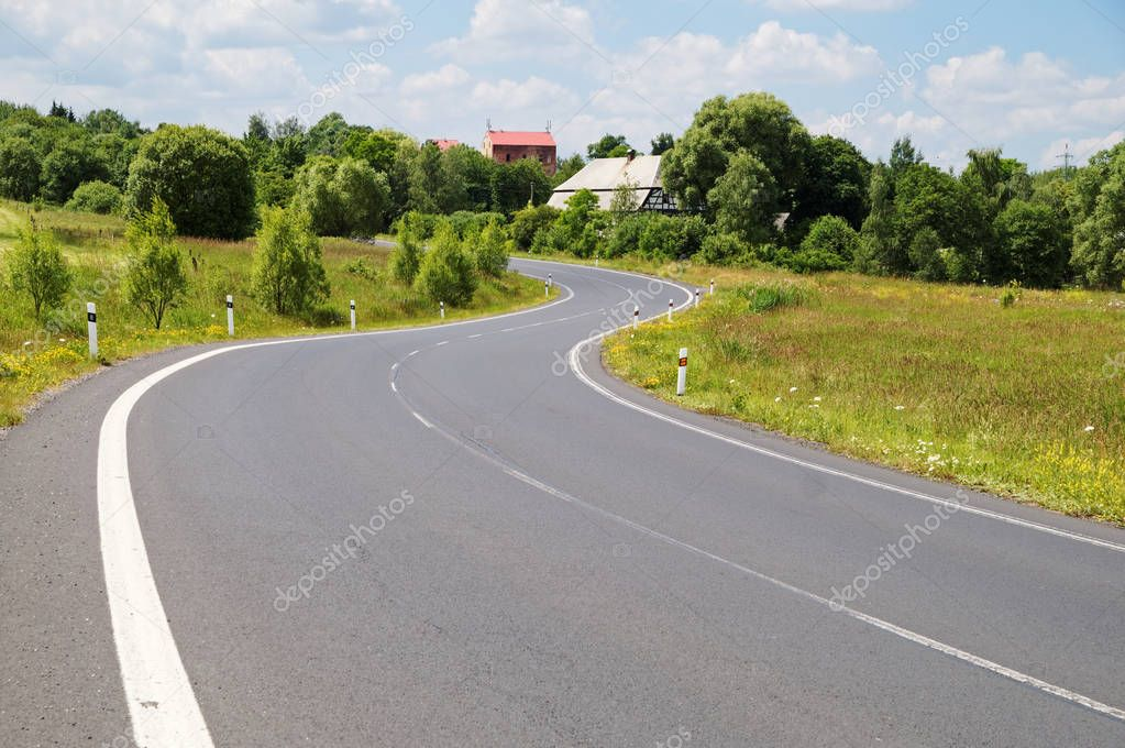 Empty asphalt road with a double bend between flower meadows in the countryside. Village among the green leafy trees background. Clear sunny day with blue skies and white clouds.