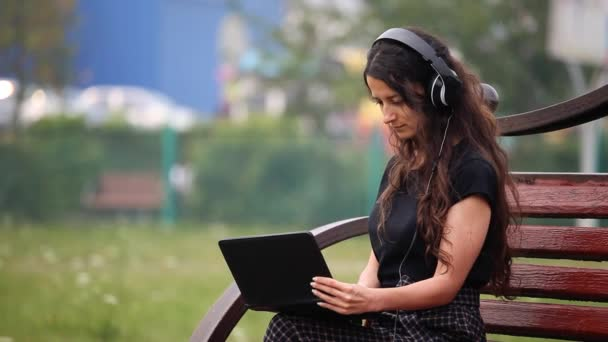 Young woman on a bench with headphones and laptop listening to music
