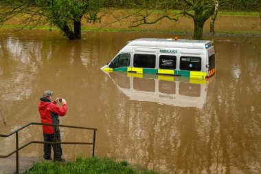 NANTGARW, NEAR CARDIFF, WALES - FEBRUARY 2020: person taking a picture of an ambulance submerged in storm water after the River Taff burst its banks near Cardiff.