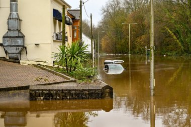 NANTGARW, NEAR CARDIFF, WALES - FEBRUARY 2020: Cars submerged and buildings flooded after the River Taff burst its banks near Cardiff.