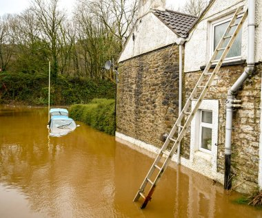 NANTGARW, NEAR CARDIFF, WALES - FEBRUARY 2020: Ladder against house and a car submerged in  floodwater on a road after the River Taff burst its banks near Cardiff.