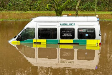 NANTGARW, NEAR CARDIFF, WALES - FEBRUARY 2020: Ambulance submerged in storm water after the River Taff burst its banks near Cardiff. Very heavy rain fell on South Waes from Storm Dennis