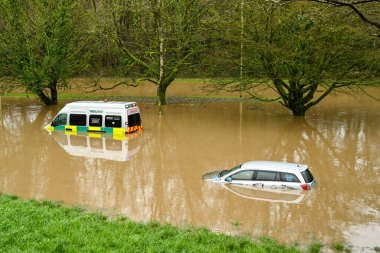 NANTGARW, NEAR CARDIFF, WALES - FEBRUARY 2020: Car and an ambulance submerged in storm water after the River Taff burst its banks near Cardiff. Heavy rain fell on South Wales from Storm Dennis.