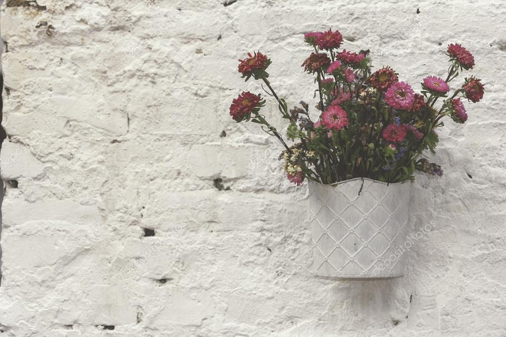 Single White Metal Planter With Bouquet Of Pink Flowers Decorating Clear Brick Wall Stock