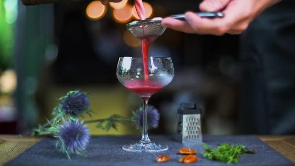 Der rote Cocktail ergießt sich ins Glas. Barmann gießt einen roten Cocktail ins Glas. Das Glas steht auf dem Tisch, auf dem der alkoholische Cocktail ausgeschenkt wird. Food Styling Restaurant