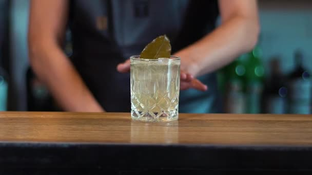 Der Barkeeper schiebt das Glas die Theke hinunter. Der Barmann hat einen Cocktail zubereitet. Bereit für einen leckeren Cocktail.