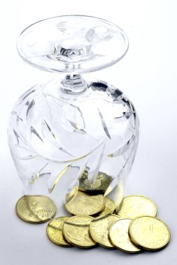 coins of dollar are poured from the glass