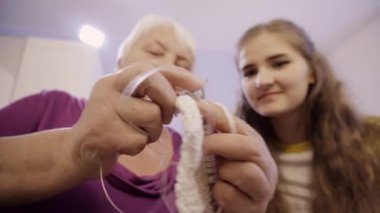 An Elderly Woman and a Girl Knits on Spokes, Old and young hands on the spokes knits a scarf for winter