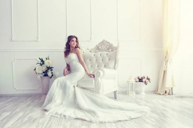 bride sitting in antique armchair