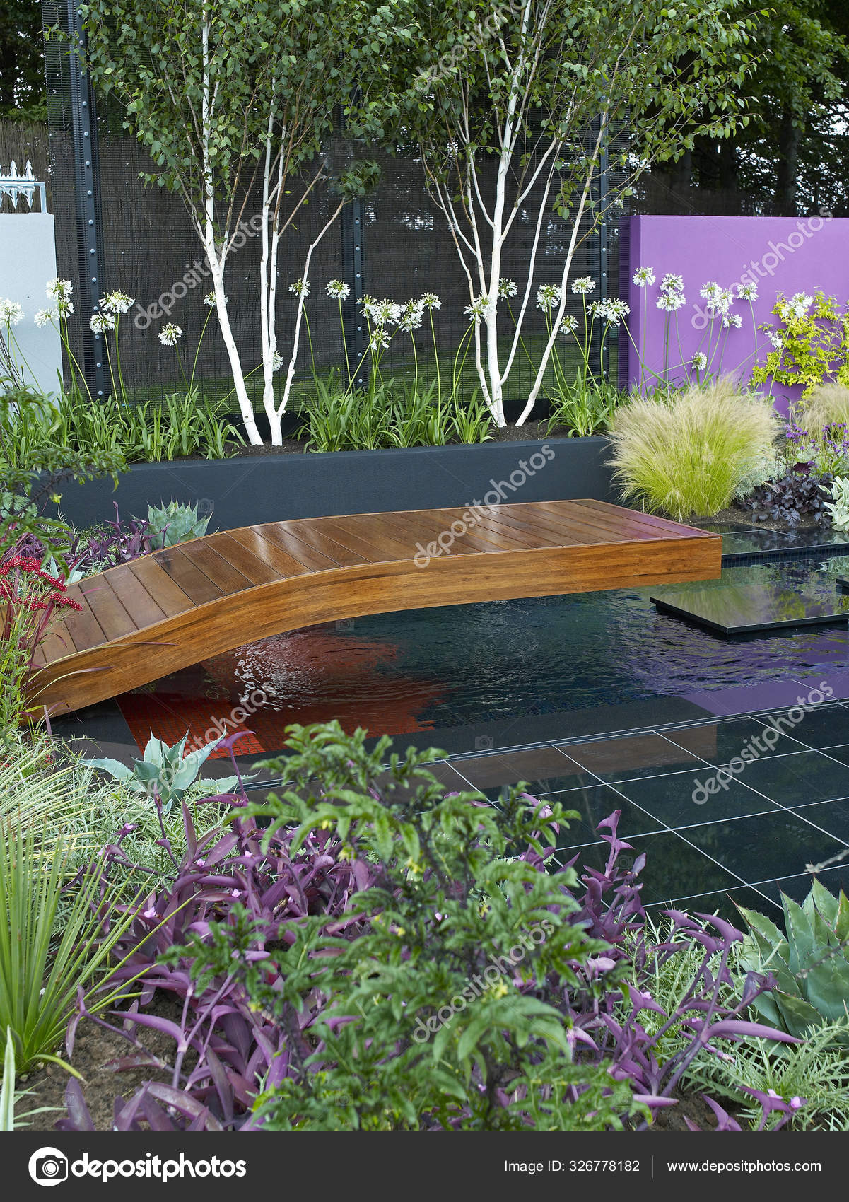 A colourful modern garden design with a range of flowers, plants and  shrubs, decking, water and architectural features 9