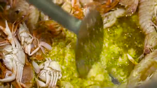 Smažení a míchání různých mořských plodů s garlik ve velké pánvi. Detailní záběr