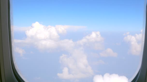 View of blue sky and clouds through an airplane window.