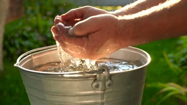 Mužské ruce spadnout do vody. Sluneční světlo. Detail