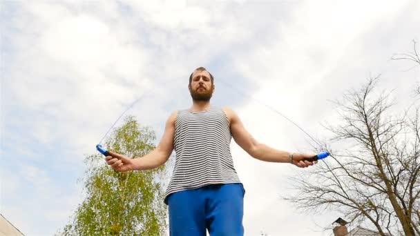 ein Mann von kräftiger Statur springt auf einem Seil