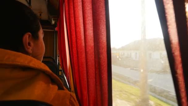 Dívka jede autobusem a dívá se z okna. Zpomal. Jízda veřejnou dopravou. Detailní záběr