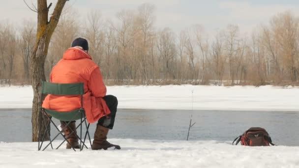 Ein Mann in orangefarbener Jacke fängt im Winter Fische. Am Ufer eines eisigen Flusses. Ufer im Schnee