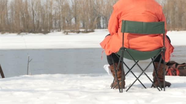 Ein Fischer sitzt auf einem Hocker und fängt im Winter Fische. Flusslauf. Zeitlupe