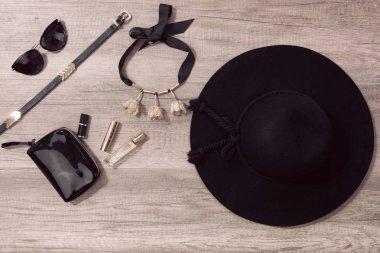 Beautiful women's minimal set of fashion accessories on wooden b