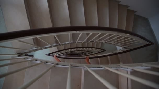 young girls walk down brown winding staircase close view