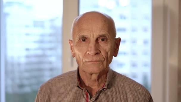 starší plešatý muž s hnědýma očima stojí v okně detailní