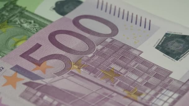 pink euro banknote lies on green face value and rotates