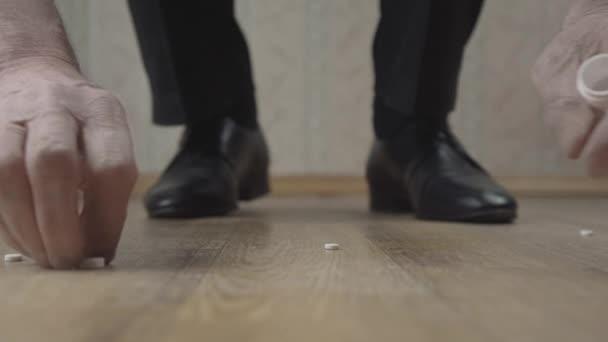 Weiße Pillen fallen auf braunen Boden und Rentnerhände sammeln sich