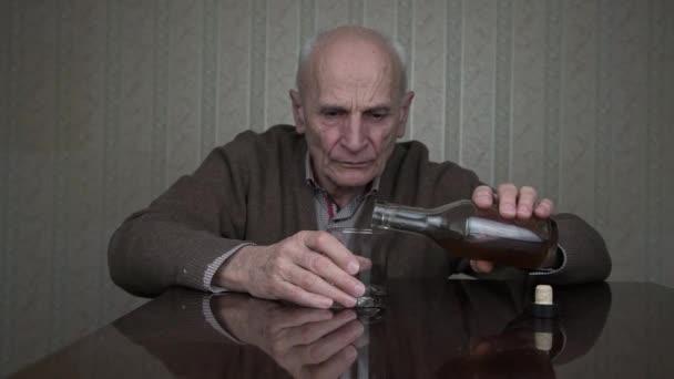 senior muž pije koňak drží sklo v třesoucích se rukou