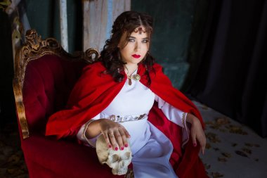 A woman witch sits in a red antique chair holds a white skull of plaster.