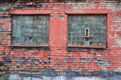 Régi vörös téglafal. Shabby ősi fal ház törött ablakokkal.