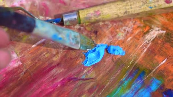 Olejomalba. Umělec míchá barvu na paletě.