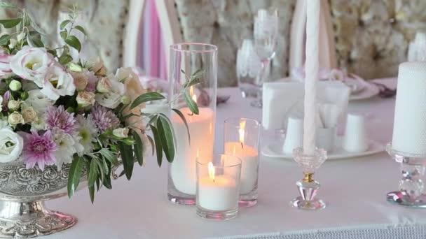 Svatební stůl zdobený krásnou kytici růží a tři svíčky