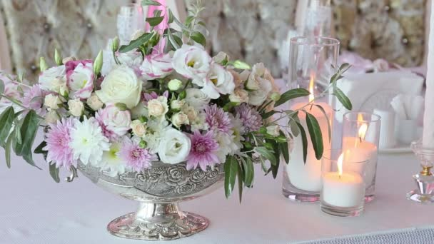 schöner Strauß Rosen und drei Kerzen auf dem Hochzeitstisch