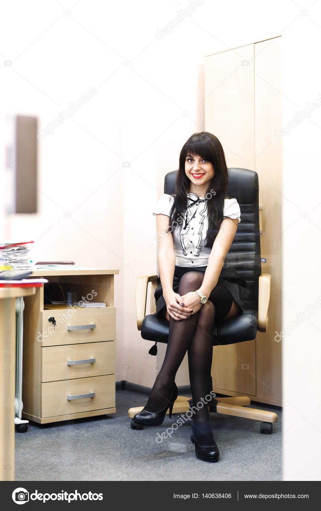 young sexy woman in black stockings sitting on workplace in offi