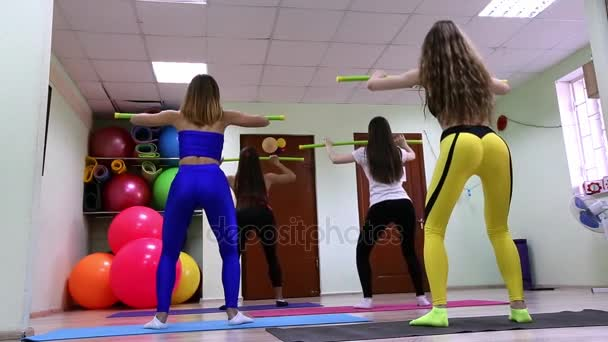 Group of young caucasian women doing exercises sit ups in a fitness club.