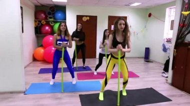 Group of young caucasian women doing exercises with stick standing in fitness studio