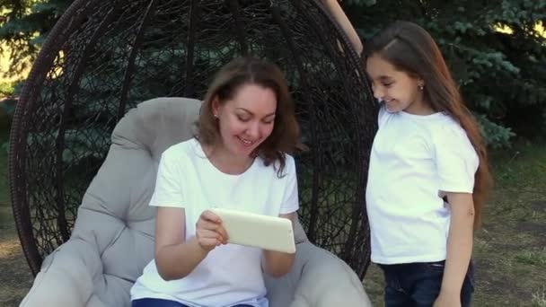 Happy mother and daughter using white tablet PC, sitting in a park at summer day