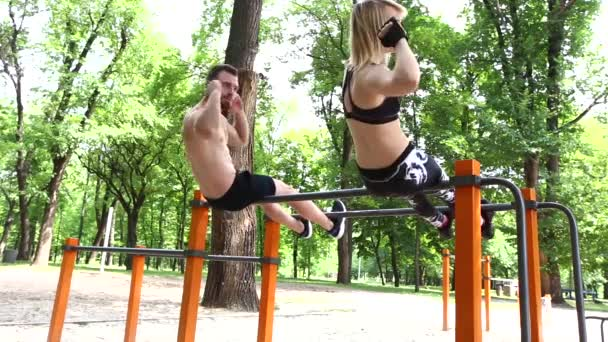 Sportovní blondýna mladá žena a vousatý muž čerpání břišní svaly v parku. Koncept zdravého životního stylu, hubnutí.